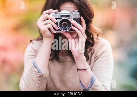 Giovane donna fotografare con fotocamera reflex in foresta di autunno Foto Stock