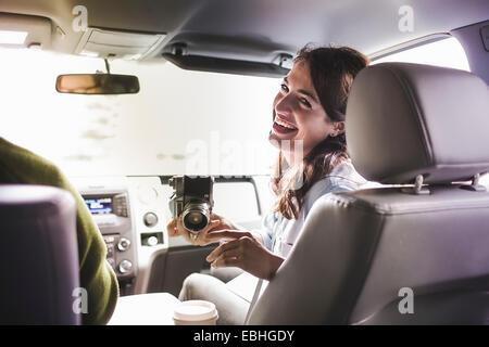 Sulla spalla vista della giovane donna in auto anteriore sedile con SLR Fotocamera Foto Stock