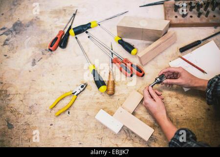 Le mani del giovane azienda craftswoman componente in organo a canne workshop Foto Stock