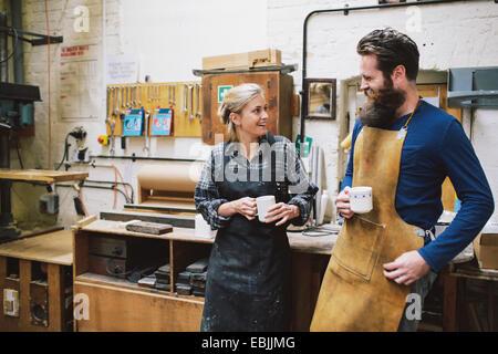 Artigiano e la donna in chat con organo a canne workshop Foto Stock