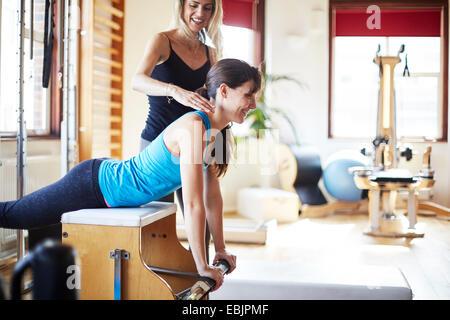 Giovane studentessa spingendo verso l'alto dal combo chair in palestra pilates