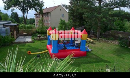 I bambini giocando divertito su un castello gonfiabile in un giardino, Germania Foto Stock