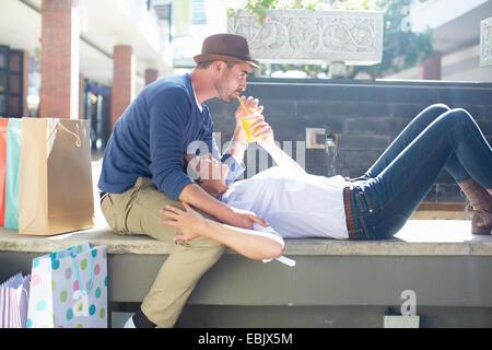 Metà adulto giovane rilassante sul sedile, bere drink, borse per lo shopping accanto a loro. Foto Stock