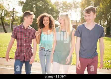 Quattro giovani amici adulti passeggiando nel parco
