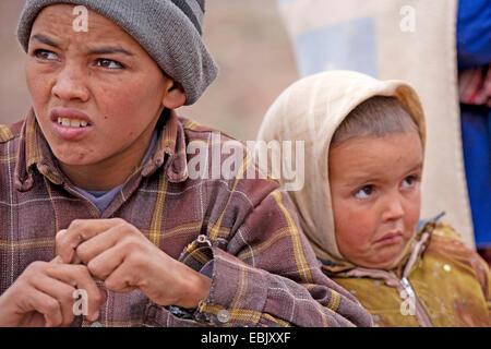 Due fratelli poveri distressed seduta accanto a ciascun altro, Marocco, Souss-Massa-Dara, Djebel Sarhro, Antiatlas Foto Stock