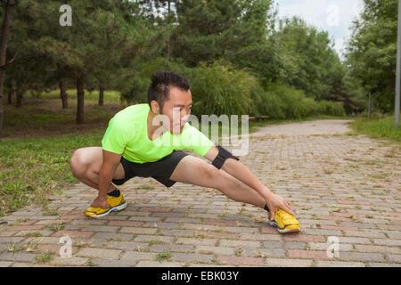 Giovane maschio runner accovacciato e stretching in posizione di parcheggio Foto Stock