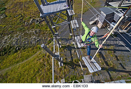 Uomo maturo a piedi su tavole di legno sulla corda alta corso Foto Stock