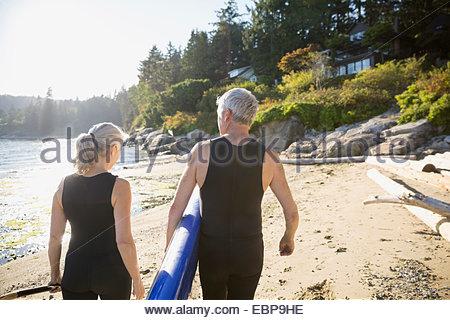 Coppia senior con paddle board di sunny beach Foto Stock
