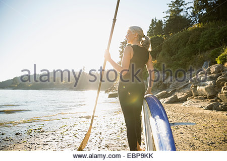 Donna senior con paddle board di sunny beach Foto Stock
