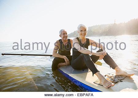 Coppia senior sulla scheda di racchetta in ocean Foto Stock