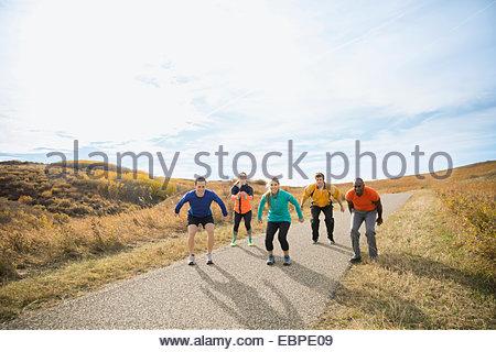Gruppo di fitness di saltare sul percorso rurale Foto Stock