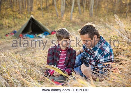 Padre e figlio utilizzando digitale compressa tenda esterna Foto Stock