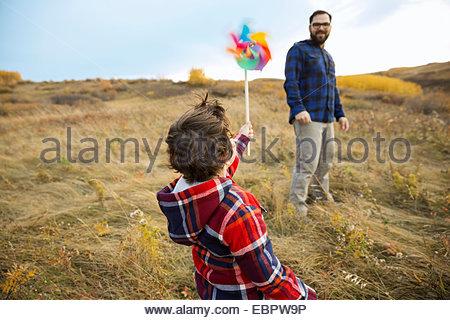 Padre guarda il figlio con la girandola in campo rurale Foto Stock