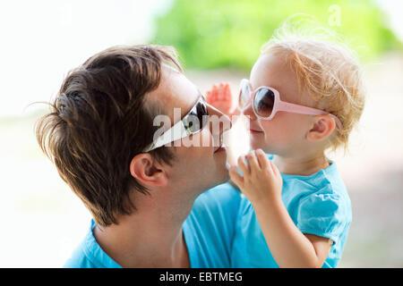 Giovane padre e figlia piccola sul suo braccio felicemente che ognuno guarda negli occhi dell'altro attraverso i Foto Stock
