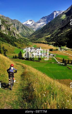 Giovani mountain biker guidando attraverso il prato di montagna a valle idilliaca, Francia, Savoie, Champagny en Foto Stock