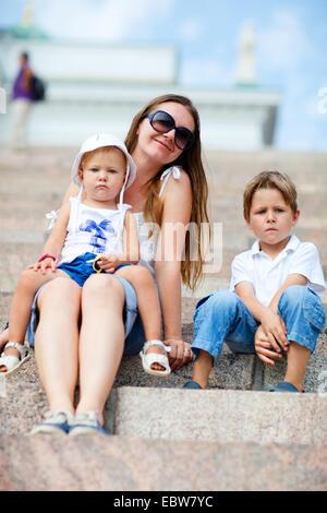 Giovane madre seduta con i suoi due bambini piccoli su scale in pietra Foto Stock
