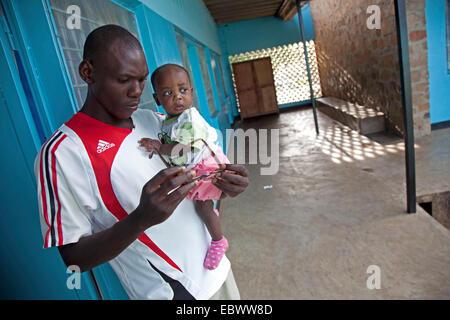 Giovane con un bambino sul suo braccio è in piedi in un corridoio pensieroso guardando i suoi occhiali, Burundi Foto Stock