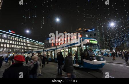 Christmas Shopper intorno a Zurigo tram treno su Zurigo Paradeplatz sotto festosa luminarie di Natale. Foto Stock