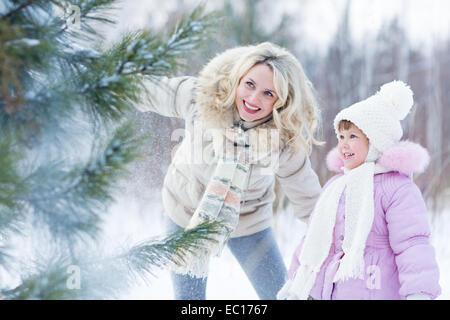 Felice genitore e bambino che gioca con la neve in inverno per esterno Foto Stock