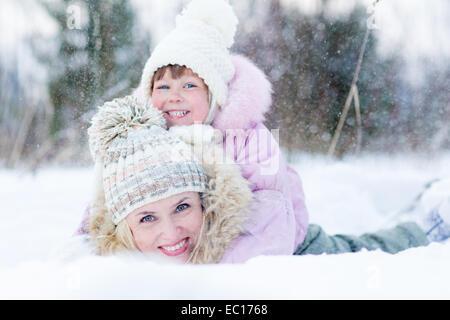 Felice genitore e bambino gioca con la neve in inverno per esterno Foto Stock