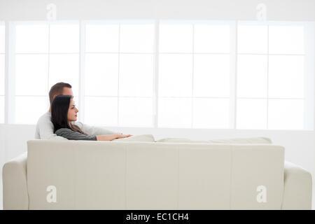 Vista laterale della giovane coppia caucasica rilassante insieme sul divano guardando nella parte anteriore Foto Stock