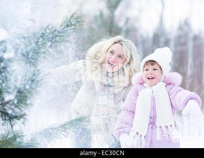 Felice mopther e kid giocando con la neve in inverno per esterno Foto Stock