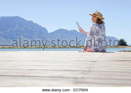 Senior donna seduta sul molo con tavoletta digitale Foto Stock