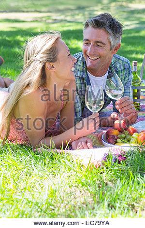 Giovane bere un vino avente un picnic Foto Stock