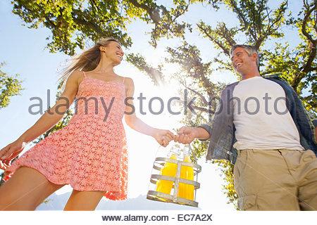 Giovane a piedi con bottiglie di picnic in campagna Foto Stock