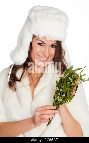 ... Che vogliono un bacio donna con mazzo di vischio indossando cappello di  pelliccia e cappotto di a15b7210f35c