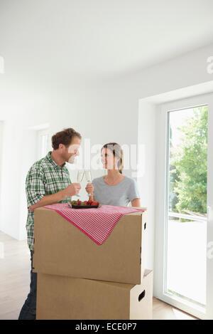 Coppia felice nuova casa celebrando bere Foto Stock
