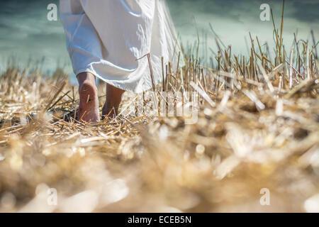 Primo piano di una giovane donna che cammina a piedi nudi attraverso un campo