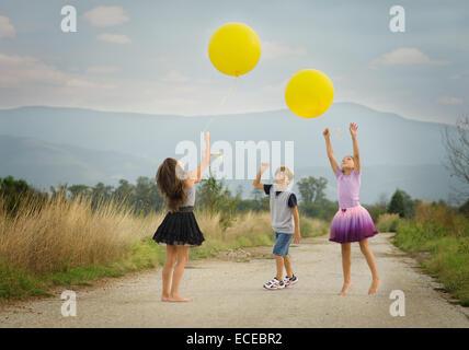 Bambini (6-7, 8-9) giocando con palloncini Foto Stock