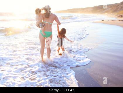La madre a piedi in surf lungo la spiaggia sabbiosa, portando il suo figlio (2-3) e portando la figlia a mano Foto Stock