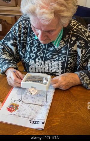 Donna anziana che soffre di presbiopia / miopia / miopia guardando cruciverba attraverso la lente di ingrandimento Foto Stock