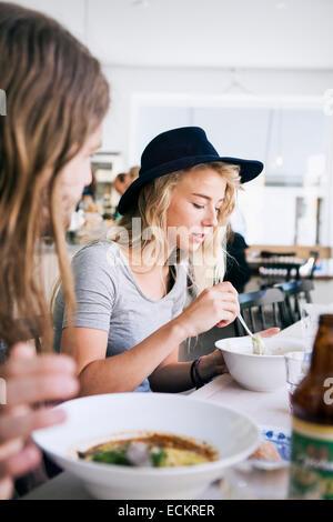 Giovane avente il cibo del ristorante Foto Stock