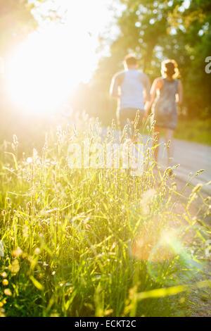 Erba che cresce in campo con il giovane a camminare sulla strada sterrata in background Foto Stock