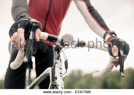 Sezione mediana del ciclista seduto su mountain bike contro il cielo chiaro Foto Stock