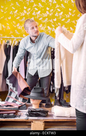 Proprietario maschio femmina aiutano il cliente nella boutique Foto Stock