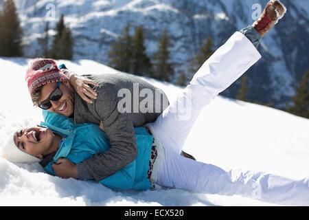 Coppia esuberante che stabilisce nella neve Foto Stock