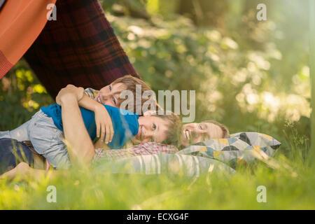 Padre e figli insieme rilassante vicino alla tenda da campeggio Foto Stock