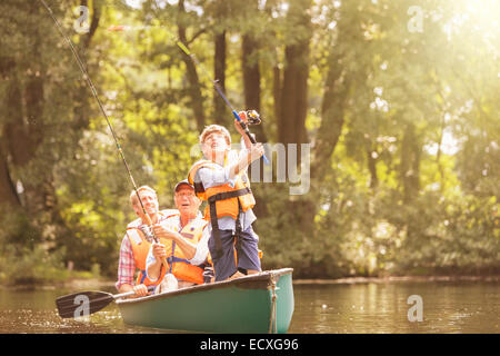 Il ragazzo, padre e mio nonno pesca in canoa sul lago Foto Stock