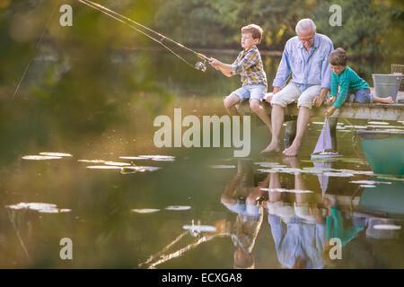 Nonno e nipoti la pesca e giocare con il giocattolo in barca a vela sul lago Foto Stock