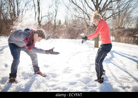 Coppia caucasica avente lotta con le palle di neve Foto Stock