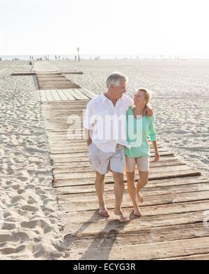 Coppia caucasica camminando sulla passerella in legno sulla spiaggia Foto Stock