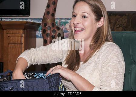 20's donna seduta su una sedia. Lei è sempre sorridente e ha bretelle. Foto Stock
