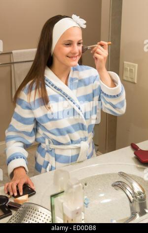 Ragazza giovane (12-13) cercando in specchio mentre si applica il trucco Foto Stock