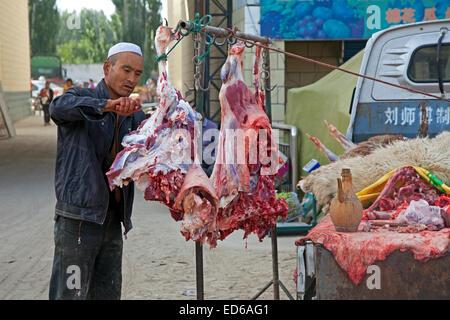 Butcher il taglio di carne dal suo pickup truck nel villaggio Waxxari, oasi cittadina nel deserto Taklamakan, provincia Foto Stock
