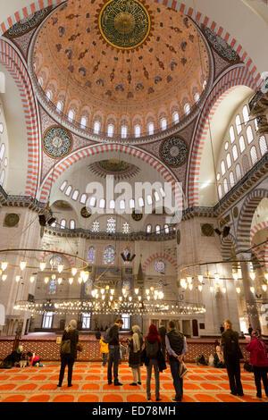 I turisti che indossa sciarpe in interno della Moschea Suleymaniye in Istanbul, Repubblica di Turchia Foto Stock