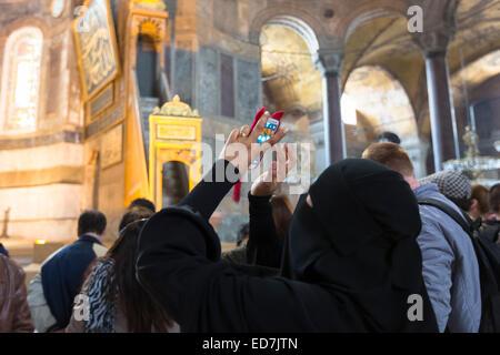 Donna musulmana a Hagia Sophia, Ayasofya Muzesi museo della moschea di indossare niqab utilizza lo smartphone per Foto Stock